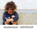 Small photo of poor, sad little child girl sitting against the concrete wall