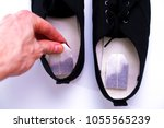 Small photo of hand puts the tea bag in shoes. concept of removing unpleasant odors