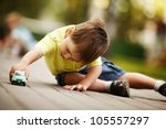 little boy plays with toy car | Shutterstock . vector #105557297