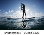 Small photo of young female paddles a paddleboard off a Bahamian island