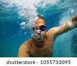 Small photo of Close up view of young adventuristic bearded man with googles diving in the exotic turquoise sea with a lot of bubbles around him.