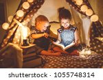 children boy and girl reading... | Shutterstock . vector #1055748314