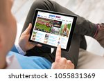man reading sports news on... | Shutterstock . vector #1055831369