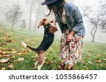 Stock photo woman walking her beagle dog in town 1055866457