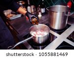 Small photo of Chef is adding white wine to a meat dish at commercial kitchen, toned, film grain, noise added