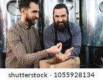 two adult bearded men check... | Shutterstock . vector #1055928134