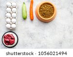 Stock photo dry organic pet food with fresh vegetables eggs and meat in plastic bowl for feeding dogs on stone 1056021494