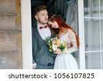 the groom and the bride stand... | Shutterstock . vector #1056107825