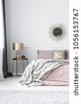 Stock photo lamp on gold table next to pink bed with grey blanket against the wall with mirror in bedroom 1056153767