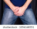 Small photo of Close up of a man with hands holding his crotch dark background.