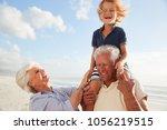 grandparents carrying grandson... | Shutterstock . vector #1056219515