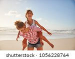 mother carrying daughter on... | Shutterstock . vector #1056228764