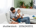 father feeding his baby son... | Shutterstock . vector #1056243551