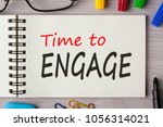 Small photo of Time to Engage written in notebook with marker pen and glasses on wooden desk. Business Concept. Top view.