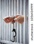 Small photo of prisoner hands behind jail bar background.