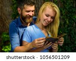 Small photo of Girl with happy face holds old book. Couple spend time together and read funny stories. Reading humor concept. Couple in love hugs outdoor and laughing, nature background, defocused.