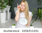 woman cleaning face with white... | Shutterstock . vector #1056511331