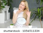 woman cleaning face with white... | Shutterstock . vector #1056511334
