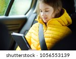 adorable girl sitting in a car... | Shutterstock . vector #1056553139