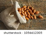 almonds in small sack on wooden ... | Shutterstock . vector #1056612305