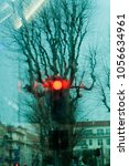 Small photo of vertical altered image of distorted trees without leaves with red traffic light