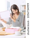 happy woman unboxing a parcel...   Shutterstock . vector #1056734999