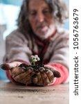 senior man holding a dainty... | Shutterstock . vector #1056763679