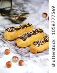 Small photo of Delicious eclairs with chocolate and hazelnut on the light background. Eclair isolated