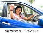 Small photo of Young Asian female showing off car key while being in the driver's seat of a blue car.
