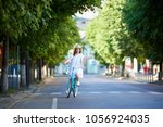 young woman rides on the road... | Shutterstock . vector #1056924035