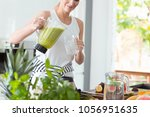 happy woman pouring a green...   Shutterstock . vector #1056951635
