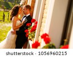 bride and groom near red flowers | Shutterstock . vector #1056960215