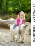 cute little girl petting and... | Shutterstock . vector #1056961487
