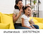 mother combing beautiful... | Shutterstock . vector #1057079624