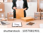 young woman preparing parcel... | Shutterstock . vector #1057081901