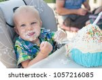Small photo of Young Caucasian Infant Baby Boy Smashes Eats Eating First Birthday Smash Cake With Frosting Icing On Face and Hands