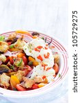 Fresh red tomatoes and mozzarella cheese salad with capers, peppers, onion, basil and croutons - stock photo