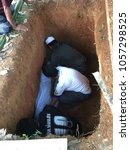 Small photo of PHANG-NGA, THAILAND - MARCH 26, 2018: Three Asian men bury a dead person covered with white cloth into a big hole underground.