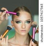 hands apply makeup on model...   Shutterstock . vector #1057417565