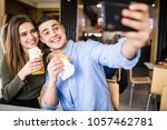 happy couple eating burger and... | Shutterstock . vector #1057462781