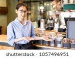 cheerful barista showing coffee ... | Shutterstock . vector #1057496951