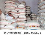 man relaxing on bags of rice in ... | Shutterstock . vector #1057506671