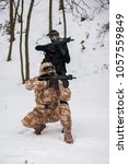 Small photo of Two airsoft models posing in the forest, snowm replica weapon, aiming