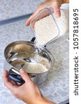 Small photo of hand impose into pan rice groats from jar