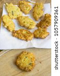 Small photo of single fried corn fritter near a dish full of the same crisp fritters