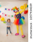 Small photo of clown girl on the birthday of a child. A party for a child. Emotional Child fools around