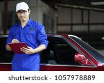young mechanic holding check... | Shutterstock . vector #1057978889