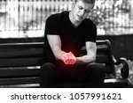 man holding sore wrist in his... | Shutterstock . vector #1057991621