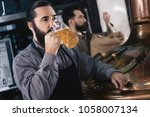 bearded brewer in apron tastes... | Shutterstock . vector #1058007134
