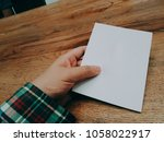 a man opens a leaflet on his... | Shutterstock . vector #1058022917